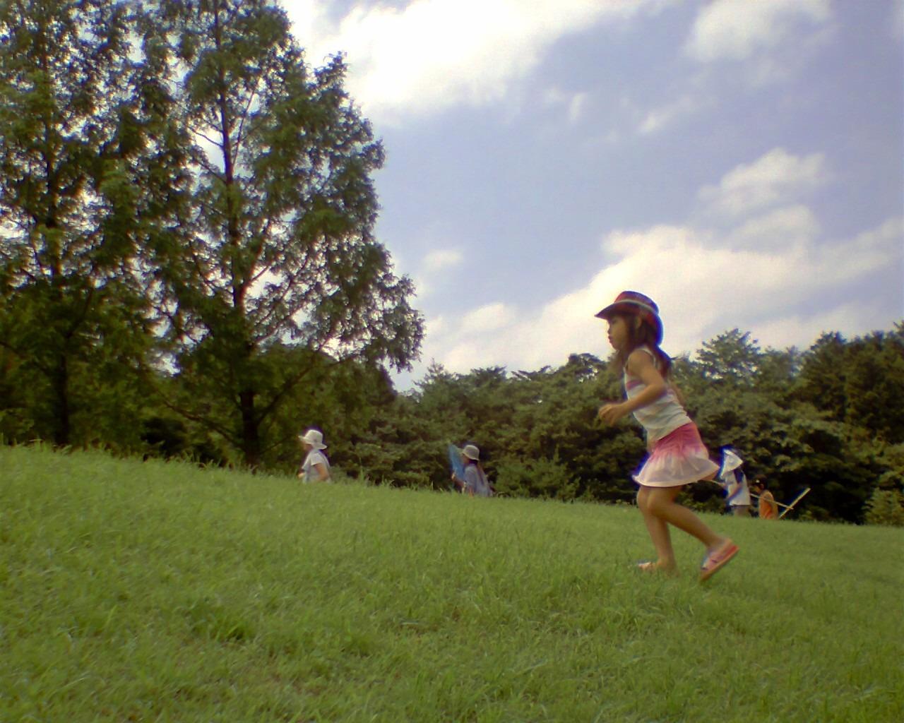 水辺に遊んだ帰りの幼女。サマー・シーズン仕様のキャミソールに同じく夏を... 芝生の上を駆け去る